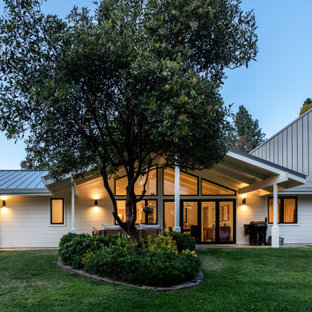 Mid-century modern white two-story exterior home idea in Sacramento with a metal roof