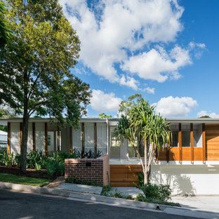 Midcentury two-storey multi-coloured house exterior in Brisbane with mixed siding and a flat roof.