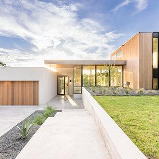 Cette photo montre une grand façade de maison beige moderne de plain-pied avec un revêtement mixte et un toit plat.