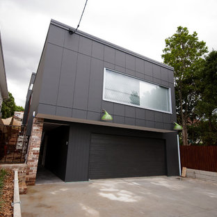 Large industrial black two-story adobe exterior home idea in Brisbane