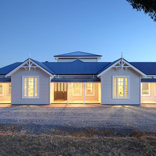 Expansive country one-storey white house exterior in Adelaide with vinyl siding, a gable roof and a metal roof.