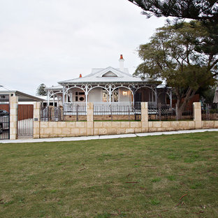 This is an example of a traditional two-storey white house exterior in Perth with wood siding, a hip roof and a metal roof.