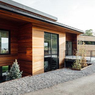 Foto de fachada de casa marrón, minimalista, de dos plantas, con revestimiento de madera y tejado plano