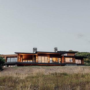 Неиссякаемый источник вдохновения для домашнего уюта: большой, двухэтажный, разноцветный частный загородный дом в современном стиле с комбинированной облицовкой, плоской крышей и зеленой крышей