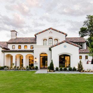 Inspiration för ett medelhavsstil vitt hus, med två våningar, stuckatur och sadeltak