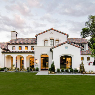 Tuscan beige split-level stucco gable roof photo in Dallas