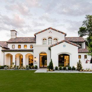 Beigefarbenes Mediterranes Haus mit Putzfassade und Satteldach in Dallas