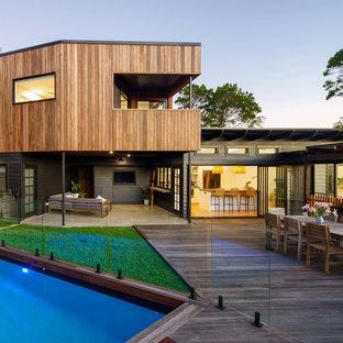 Ejemplo de fachada de casa negra, minimalista, de tamaño medio, de tres plantas, con revestimiento de madera, tejado a doble faldón y tejado de metal