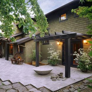 Modelo de fachada verde, de estilo de casa de campo, a niveles, con revestimiento de madera
