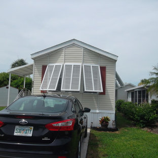 Example of a small island style beige one-story vinyl house exterior design in Miami with a hip roof and a shingle roof