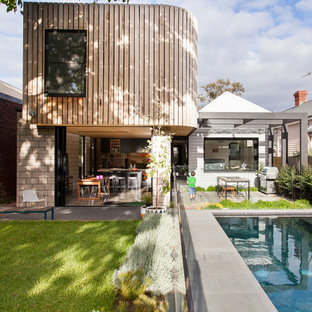 Contemporary two-story wood flat roof idea in Melbourne