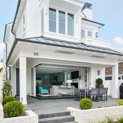 Large coastal white two-story wood exterior home idea in Orange County with a hip roof