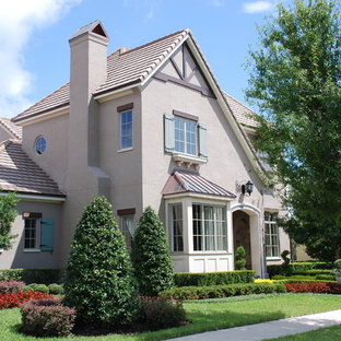 Mid-sized traditional gray two-story stucco gable roof idea in Orlando