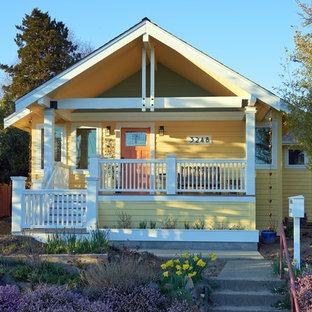 Ispirazione per la facciata di una casa unifamiliare gialla american style a due piani di medie dimensioni con rivestimento in legno, tetto a capanna e copertura a scandole