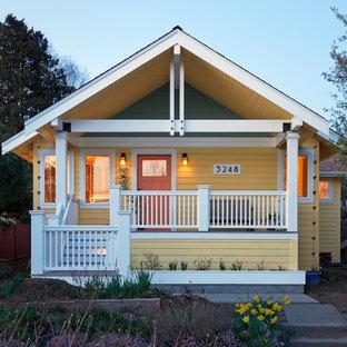 Foto della facciata di una casa unifamiliare gialla american style a due piani di medie dimensioni con rivestimento in legno, tetto a capanna e copertura a scandole