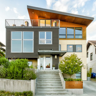 Mid-sized modern beige three-story mixed siding exterior home idea in Seattle with a shed roof