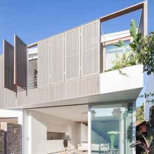 Example of a trendy white two-story stucco flat roof design in Sydney