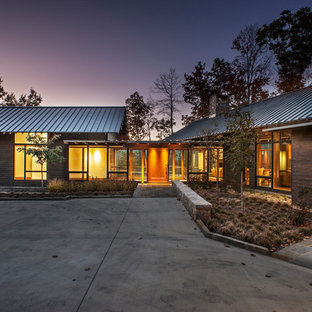 Large modern brown two-story wood exterior home idea in Charlotte with a metal roof