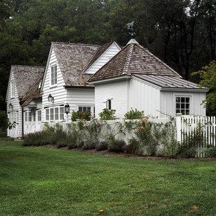 Ejemplo de fachada blanca, romántica, de dos plantas, con revestimiento de madera y tejado de varios materiales