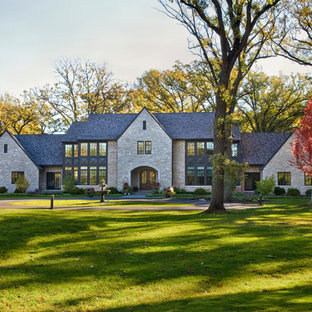 Huge elegant beige two-story stone gable roof photo in Chicago with a shingle roof