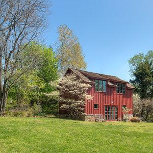Bild på ett litet lantligt rött hus, med två våningar, metallfasad, sadeltak och tak i shingel