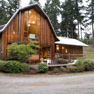 Mid-sized mountain style brown two-story wood exterior home photo in Seattle with a gambrel roof and a metal roof