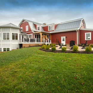 Example of a country red two-story exterior home design in Columbus with a gambrel roof