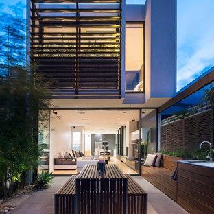 Esempio della facciata di una casa grande contemporanea a due piani con rivestimenti misti e tetto piano