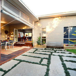 Design ideas for a modern one-storey beige house exterior in Sydney with metal siding, a flat roof and a metal roof.