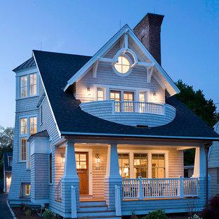 Imagen de fachada gris, costera, grande, de tres plantas, con revestimiento de madera y tejado a dos aguas