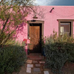 Esempio della facciata di una casa unifamiliare piccola rosa american style a un piano con rivestimento in adobe e copertura mista