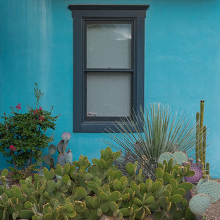 Inspiration for a small southwestern blue two-story adobe duplex exterior remodel in Other with a mixed material roof