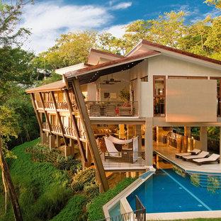 Idées déco pour une grand façade de maison beige exotique à un étage avec un revêtement en stuc, un toit en appentis et un toit en shingle.