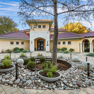 Large mediterranean beige two-story stucco house exterior idea in Austin with a hip roof and a tile roof