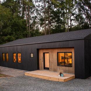 Imagen de fachada de casa negra, nórdica, pequeña, de una planta, con revestimiento de madera, tejado a dos aguas y tejado de teja de madera