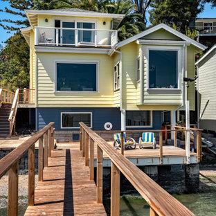 Exempel på ett litet maritimt gult hus, med tre eller fler plan, fiberplattor i betong, sadeltak och tak i shingel