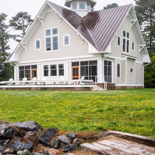 Large beach style beige two-story wood exterior home idea in Richmond with a clipped gable roof and a metal roof