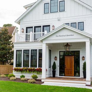 Пример оригинального дизайна: большой, трехэтажный, белый частный загородный дом в стиле кантри с облицовкой из ЦСП, двускатной крышей и отделкой дранкой