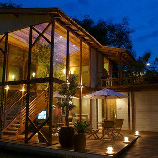 Inspiration for a tropical two-story glass exterior home remodel in Other