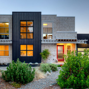 Design ideas for a contemporary two-storey black exterior in Seattle with mixed siding and a flat roof.