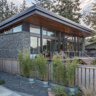 Small minimalist gray one-story stone house exterior photo in Seattle with a shed roof and a metal roof