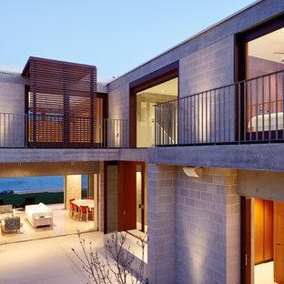 На фото: двухэтажный, серый частный загородный дом в современном стиле с облицовкой из бетона, плоской крышей и крышей из смешанных материалов