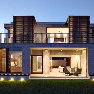 Ispirazione per la facciata di una casa unifamiliare grigia contemporanea a due piani di medie dimensioni con rivestimento in cemento, tetto piano e copertura mista