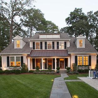 Ejemplo de fachada beige, costera, de dos plantas, con revestimiento de madera y tejado a dos aguas