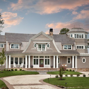 Large beach style beige three-story wood exterior home idea in DC Metro with a gambrel roof