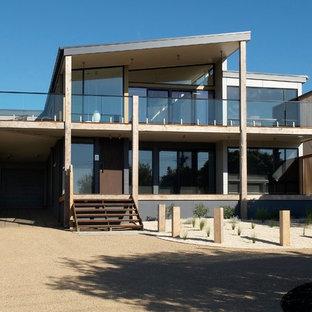 メルボルンのビーチスタイルのおしゃれな家の外観 (ガラスサイディング) の写真