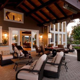 Modelo de fachada marrón, costera, de tamaño medio, de dos plantas, con revestimientos combinados y tejado a dos aguas