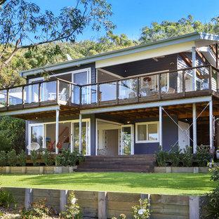 Immagine della facciata di una casa unifamiliare viola stile marinaro a due piani con tetto a capanna