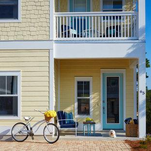 Ejemplo de fachada de casa amarilla, costera, de dos plantas, con revestimientos combinados
