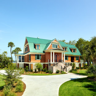 Huge beach style brown two-story wood house exterior idea in Charleston with a gambrel roof and a metal roof